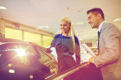 Happy woman with car dealer in auto show or salon Kuvituskuvat