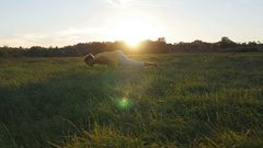 Young man practicing yoga moves and positions at green grass at the meadow Stock Footage