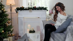 Winter holidays, girl reading a book, woman drink tea from a cup, in cozy Stock Footage
