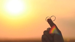 Gold rings in her hand girl on sun background Stock Footage
