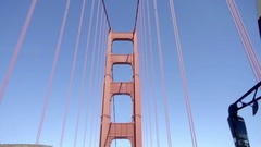 Big Bus driving across Golden Gate Bridge upward angle view with blue sky Stock Footage