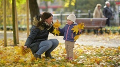 Happy Young Mother and her Little Daughter Having Fun in an Autumn Park, Mom and Arkistovideo