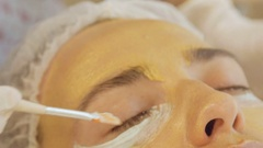 Application of golden masks on the face of the model. Close up Stock Footage