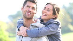 Man giving piggyback ride to girlfriend in countryside Stock Footage