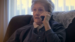 An aging senior in her 90s talks and laughs on a phone in her home in 4k dolly Stock Footage