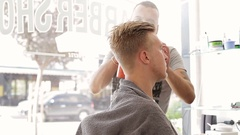 Barber puts the client's hair hairspray Stock Footage