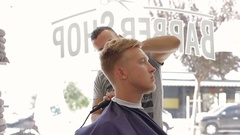 Barber shaves client's hair with trimmer Stock Footage