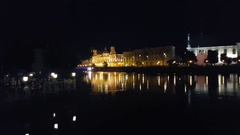 Beautiful castle under yellow & white light near river with reflection on water Stock Footage