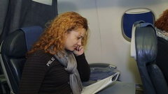 Young woman reading a magazine in an airplane flying Arkistovideo