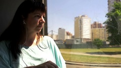 Woman riding on the bus looking out the window and drinking water Stock Footage