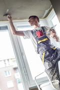 Plasterer renovating indoor walls and ceilings Stock Photos