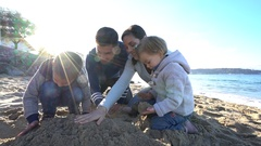 Family at the beach building up sand castle Stock Footage