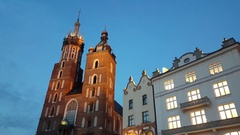 Pan from St. Mary's Basilica to Cloth Hall main square in Krakow beautiful sky Stock Footage
