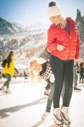 Happy family outdoor ice skating at rink. Winter activities Stock Photos