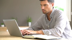 Middle-aged man working from home on laptop computer Stock Footage
