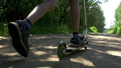 Boy riding push scooter in the playground, slow motion Stock Footage