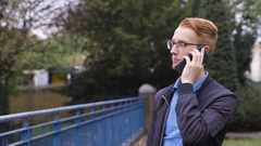 Young man with ginger hair talks on the phone Stock Footage
