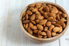 Almonds in bowl closeup. Stock Photos