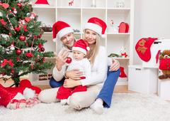 Happy family celebrating Christmas at home Stock Photos