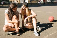 Woman and friend reading smartphone update on basketball court Stock Photos