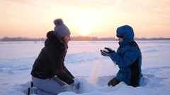Girl and child throwing snow over himself and enjoys it in winter park at sunset Stock Footage
