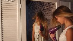 Teenage girl in white dress is dancing in front of the wardrobe mirror with hair Stock Footage