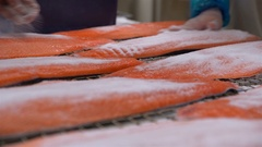 Workers applying salt on salmon fillets lying on table. Stock Footage