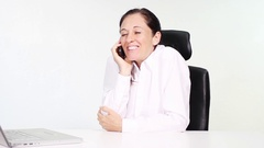 Attractive woman talking on phone amused at workplace in office Stock Footage