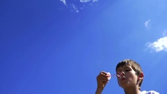 Boy Blowing Soap Bubbles Outdoors On A Sky Background, Slow Motion Stock Footage