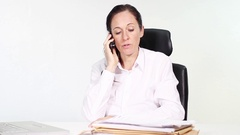 Woman in office performs serious telephoning and looks worried into blank Stock Footage