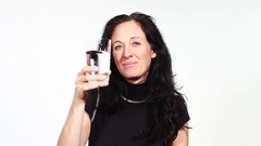 A woman looking at the camera, propping us up and drinking a glass of water Stock Footage