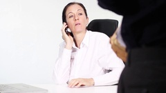 Woman in the office on the phone is unfriendlyly interrupted by the boss Stock Footage