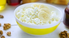Healthy breakfast - crumbly, cottage cheese with banana, walnuts, croissants Stock Footage