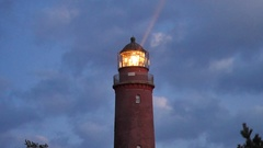 Old lighthouse above forest. Gallery with handrail around glass of spotlight. Stock Footage