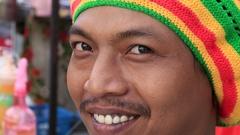 Portrait Thai man in a Rastafarian hat on street market in Koh Phangan, Thailand Stock Footage