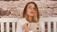 Young teenage girl feeling sick. She sitting on the bench, hugging a teddy bear Stock Footage