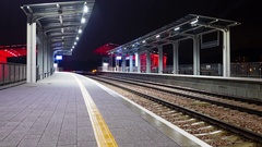 Modern railway train station at night. Bright colors and rapid blurred movement. Stock Footage