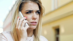 Girl looking worried while talking on cellphone in the alley Stock Footage