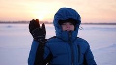 Child waving hand greeting in winter park at sunset Stock Footage