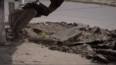 Scoop of excavator moves pieces of asphalt. Road repair, outdoors, city street. Stock Footage