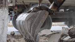 Excavator loading fragmented asphalt on a dump truck Stock Footage