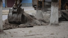 The bucket of the excavator stripping the old road surface. Stock Footage