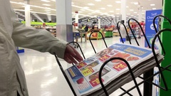 Motion of woman taking flyer inside Walmart store with 4k resolution Stock Footage