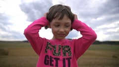 Pretty girl looks at the camera and combs her hair in the field Stock Footage