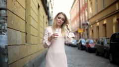 Beautiful girl in elegant dress standing in alley in old town Stock Footage