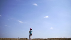 Girl making a selfie with your phone, standing agains the sky and making photo Stock Footage