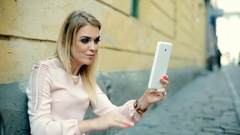 Happy girl in elegant outfit having a videocall on tablet in the alley Stock Footage