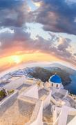 Old Town of Thira on the island Santorini, white church against colorful sunset  Stock Photos