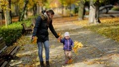 Mother and Daughter Walking Holding Hands at Park. They are Wearing Warm Clothes Stock Footage
