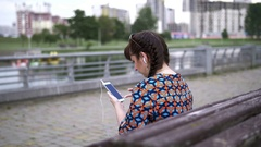 Woman sitting on a bench in the park and listening to music from your phone Stock Footage
